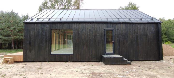 Для фасада использовалась сосновая строганая доска, покрашенная в два слоя черной краской. Ее монтировали уже на участке
